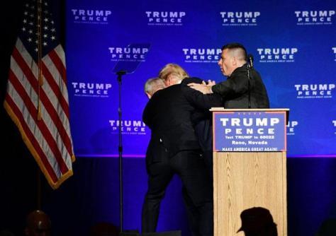5日、米西部ネバダ州で演説中、警備担当者に守られながら舞台から避難する共和党のトランプ候補(中央)(ロイター)