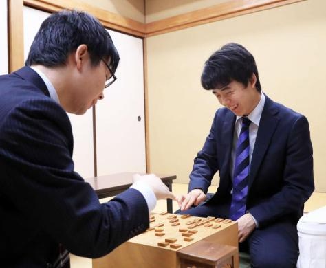 高見泰地五段(左)に勝利し感想戦を行い笑みを浮かべる藤井聡太四段(撮影・江口和貴)