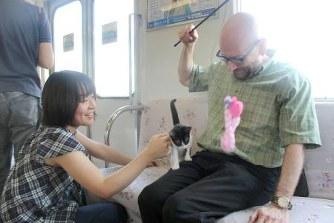 養老鉄道の「ねこカフェ列車」で子猫と触れ合う乗客=岐阜県養老町で10日
