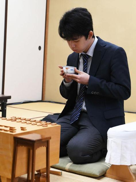 藤井四段は手にした茶に息を吹き掛けて冷ます(撮影・山崎安昭)
