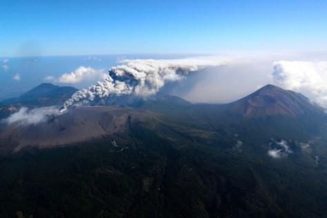 小規模噴火し、噴煙を上げる新燃岳。右は高千穂峰=11日午前10時21分、鹿児島・宮崎県境、朝日新聞社ヘリから、堀英治撮影