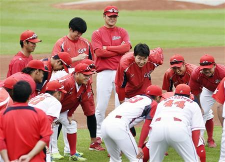 練習前、グラウンドで円陣を組む広島の選手ら。中央奥は緒方監督=マツダ