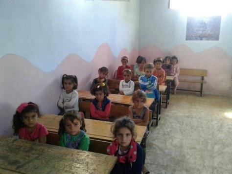 完成したTOYAMA学校の教室で学ぶ避難民のシリア人の子どもたち。腕組みは敬意を示すポーズという=シリア北西部のアトメ村で2017年9月、マゼンさん提供