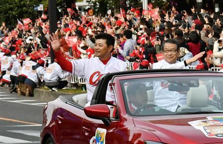 プロ野球広島カープのセ・リーグ連覇を祝うパレードで手を振る緒方監督(左)=広島市
