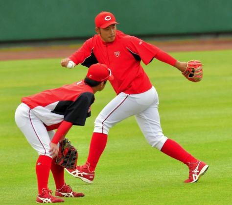 上本(左)に外野守備の指導をする広瀬コーチ