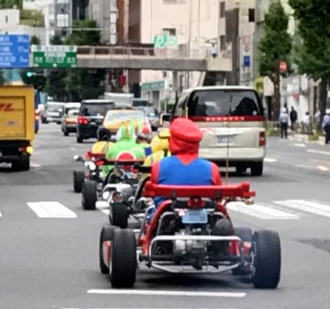 東京都内で連なって走る公道カート。ゲームのキャラクターの格好で乗る人が多い=10月4日午後、荒ちひろ撮影