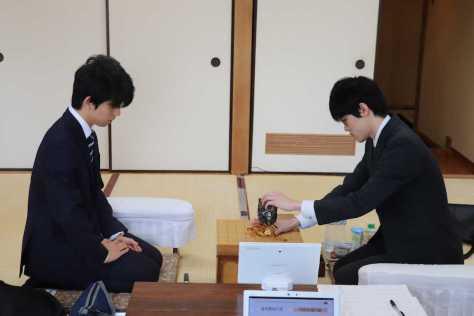 順位戦C級2組の対局前、駒袋から駒を取り出す三枚堂達也六段(右)とそれを見つめる藤井聡太六段(撮影・日本将棋連盟)
