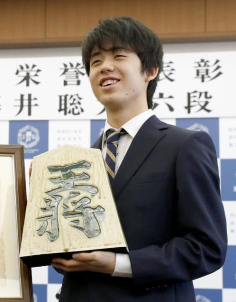 「瀬戸市民栄誉賞」が贈られ、瀬戸焼の駒の置物を手にする藤井聡太六段(共同)