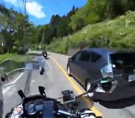 兵庫県内の男性が投稿した映像。黒色の乗用車が道志村の国道を走行中、対向車線に入り、オートバイを追い抜く様子が映っている