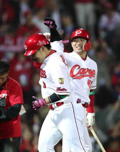 <広・巨>7回1死、丸(左)は右越えにソロ本塁打を放ち、鈴木とタッチをかわす(撮影・坂田 高浩)