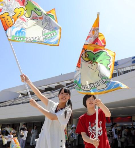 与島プラザ前で瀬戸大橋を通過するアンパンマントロッコに旗を振る福田朱里さん(左)と甲斐心愛さん=香川県坂出市の与島PA、安冨良弘撮影