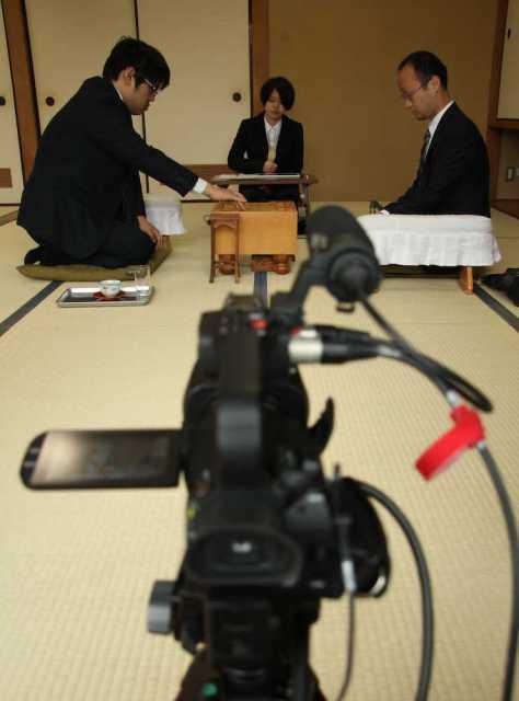 第68期王将戦挑戦者決定リーグ戦プレーオフで初手を指す糸谷哲郎八段(左)。中継カメラが静かに見守る