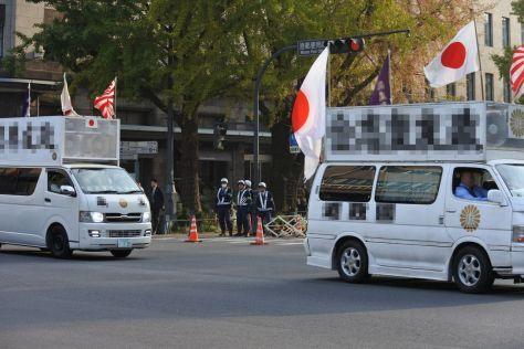 警察官がバリケードをつくる中、会場前の道路を右翼団体の街宣車が連なった=横浜市中区(画像を一部修整しています)