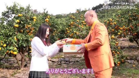 上野真歳社長が「まなまな」さんに有田みかんを渡す動画シーン