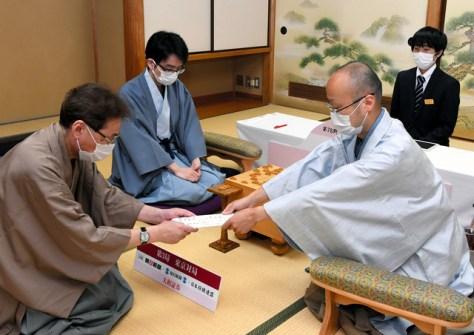 第3局で、立会人の塚田泰明九段(左)に封じ手を渡した渡辺明名人(右)=2020年6月25日、東京都渋谷区