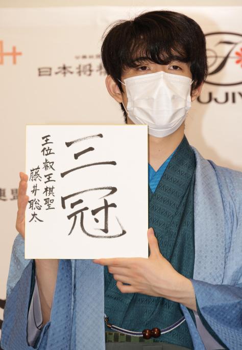 史上初の10代3冠を達成した藤井新叡王は、色紙を掲げる(撮影・中島郁夫)