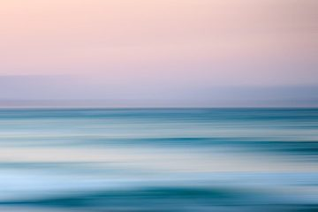 magnificent view of ocean beneath light pink sky