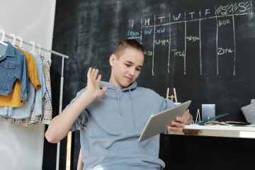 photo of boy wearing gray hoodie while using tablet