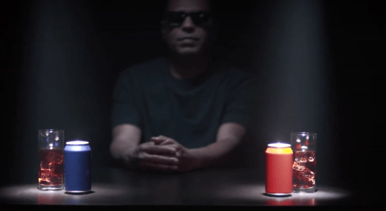 Homem de óculos escuros em frente a duas latas de refrigerante