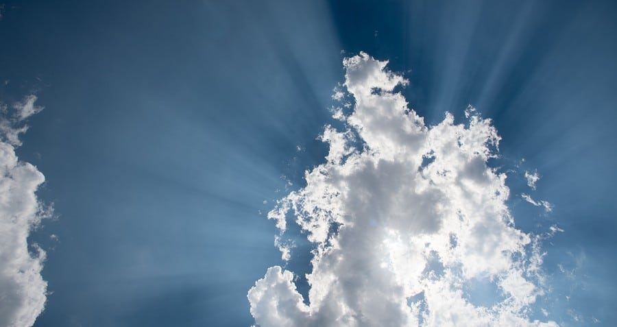 Blue sky with sun rays shining behind clouds