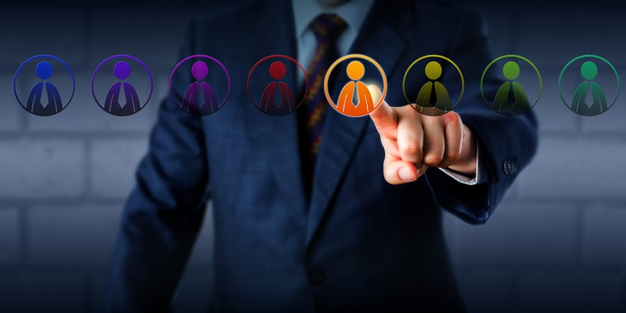 Manager is selecting one virtual worker in a lineup of eight differently colored male employee icons. Concept for multiculturalism equal opportunity employment and a business case for diversity.