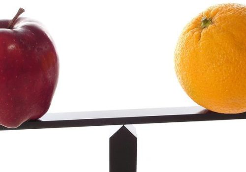 Metaphor of comparing apples to oranges on a balance beam isolated on white and the oranges are not as heavy or light, representing non-financial KPIs.