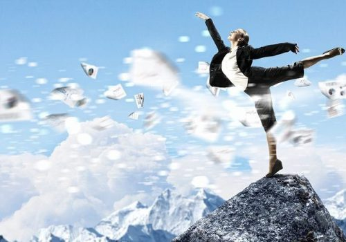 young businesswoman standing on one leg atop of mountain against diagram background, reflecting strategic finance and FP&A teams