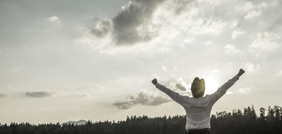 Desaturated image of victory power and success - businessman standing with his arms reaching up towards sky with his hand making fists as he celebrates his personal and business achievement--for Cloud SaaS success