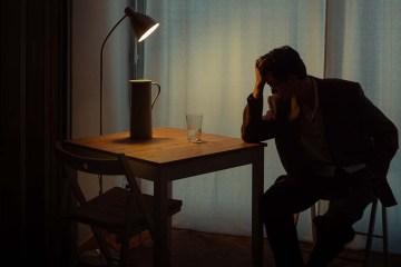 Homem de terno sentado com cotovelo sobre a mesa e escorando a testa na mão. Em cima da mesa há um abajur iluminando o ambiente, que é bem escuro e representa a depressão na advocacia