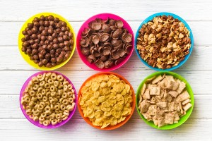 top view of various kids cereals in colorful bowls on wooden tab