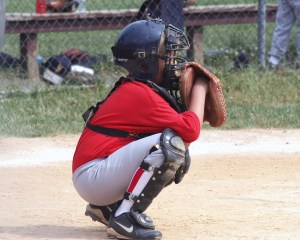 youth baseball player in catcher's uniform squatting in position