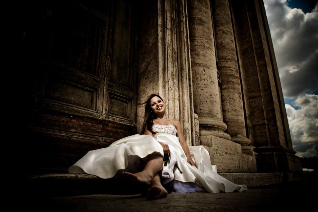 Noiva sentada na escada de uma igreja, em ensaio Trash-The-Dress com o vestido de noiva e os pés descalços.