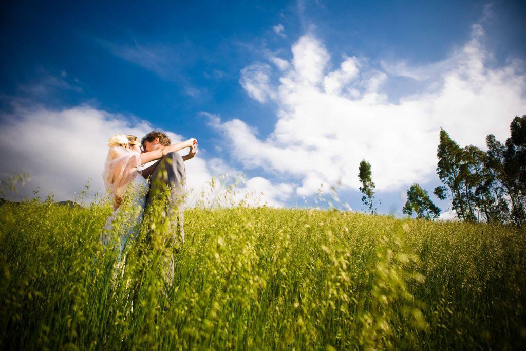 Fotografia de ensaio Trash-The-Dress com casal se beijando e grande destaque para o campo e o céu azul.