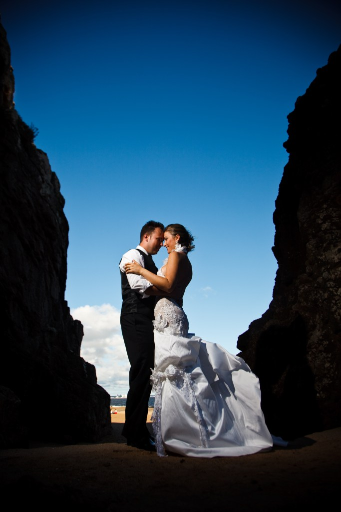 Foto com o casal na praia em ensaio fotográfico durante o dia. Noivos estão de pé, com traje formal e a noiva com um longo vestido.