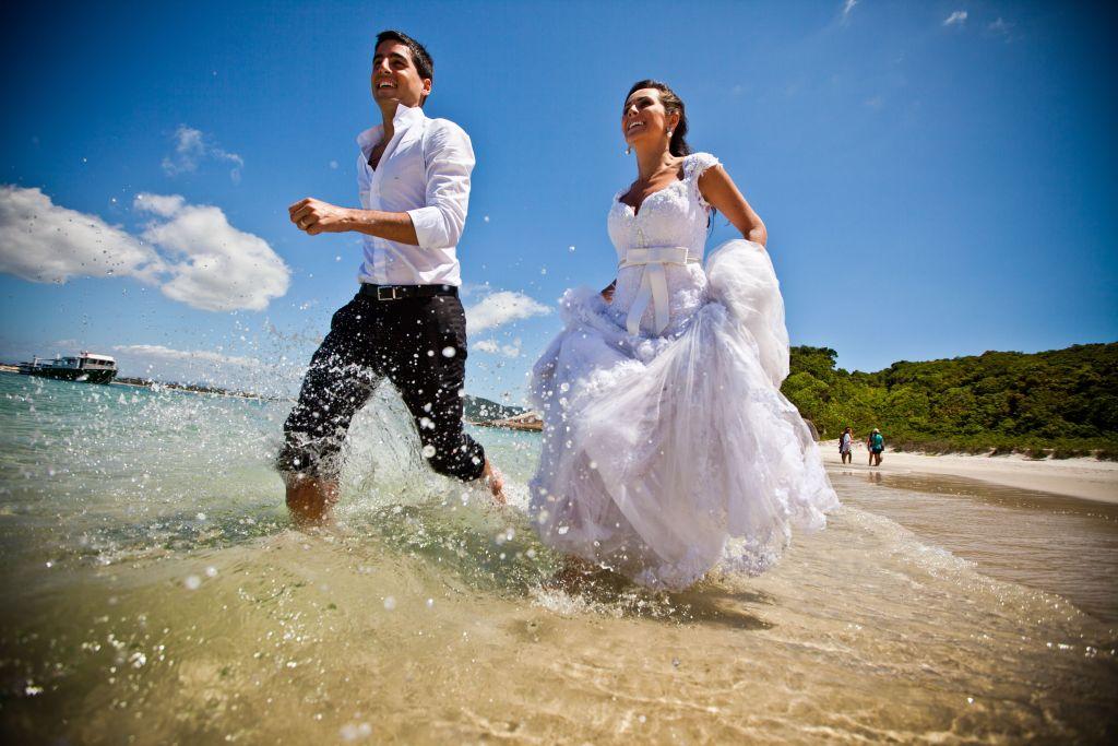 Fotografia de noivos felizes correndo na praia em ensaio fotográfico durante o dia. A noiva está segurando o vestido para não molhar muito.