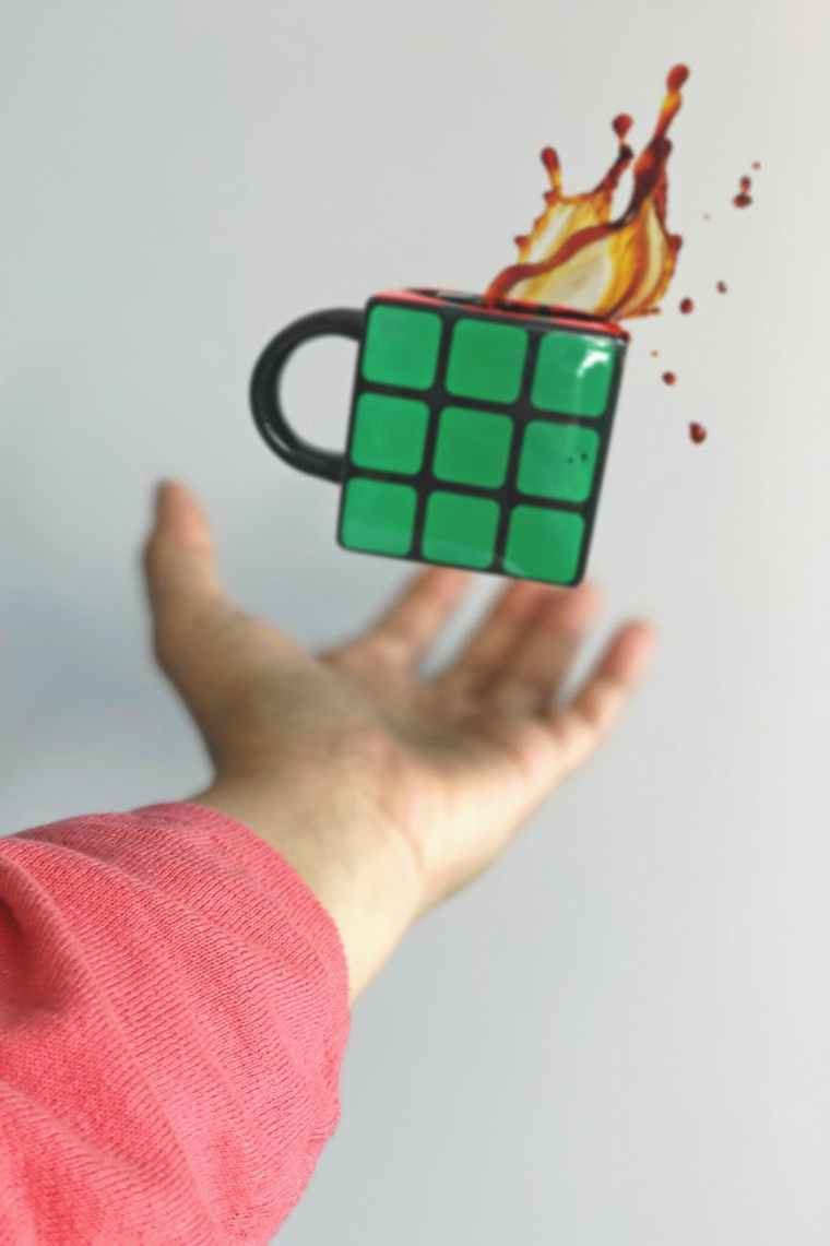 green and black coffee mug on air