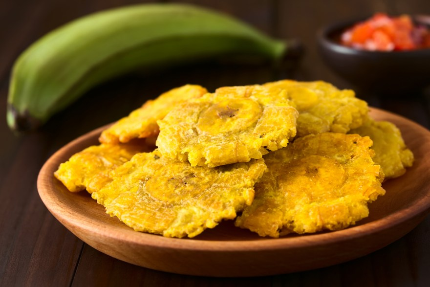 plate of tostones and green plantains in the background