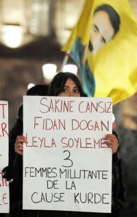 """A woman of Kurdish origin holds a sign reading """"Sakine Cansiz, Fidan Dogan, Leyla Soylemez - 3 women militants of the Kurdish cause"""" during a demonstration and commemoration in honor of the three Kurdish women activists killed yesterday in Paris, on January 10, 2013."""