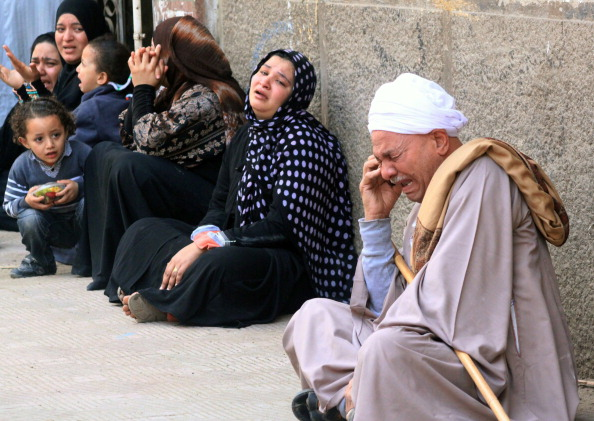 Egyptian relatives of supporters of ousted Islamist president Mohamed Morsi cry sitting outside the courthouse after the court ordered the execution of 529 Morsi supporters after only two hearings (Photo Credit: AFP/Getty Images).