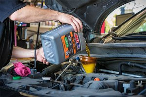 Pouring AMSOIL XL Oil into engine.