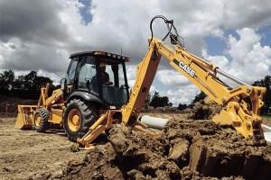 Backhoe digging up ground.