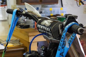 Secure handlebars to true a dirt bike rim without a stand.