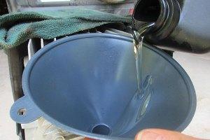 Adding air compressor oil to compressor.