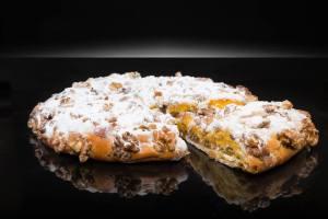 Torta Rellena. con una selección de frutas confitadas y yema, cubiertas de nueces y espolvoreadas de azúcar glas.