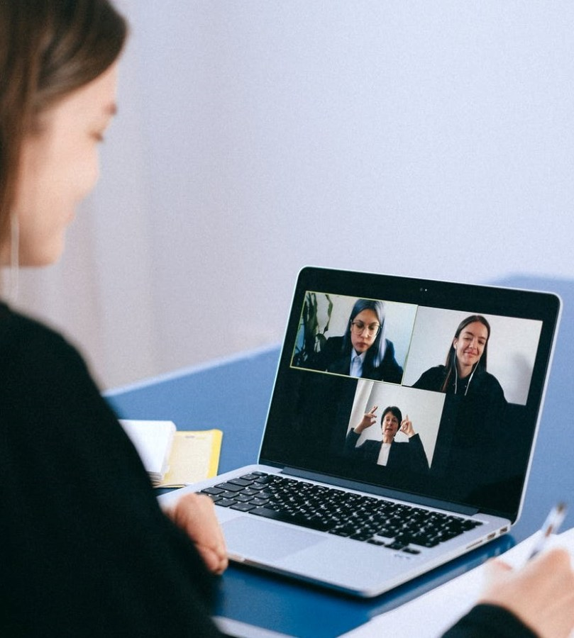 A spa owner connecting with her staff through virtual meetings on a laptop