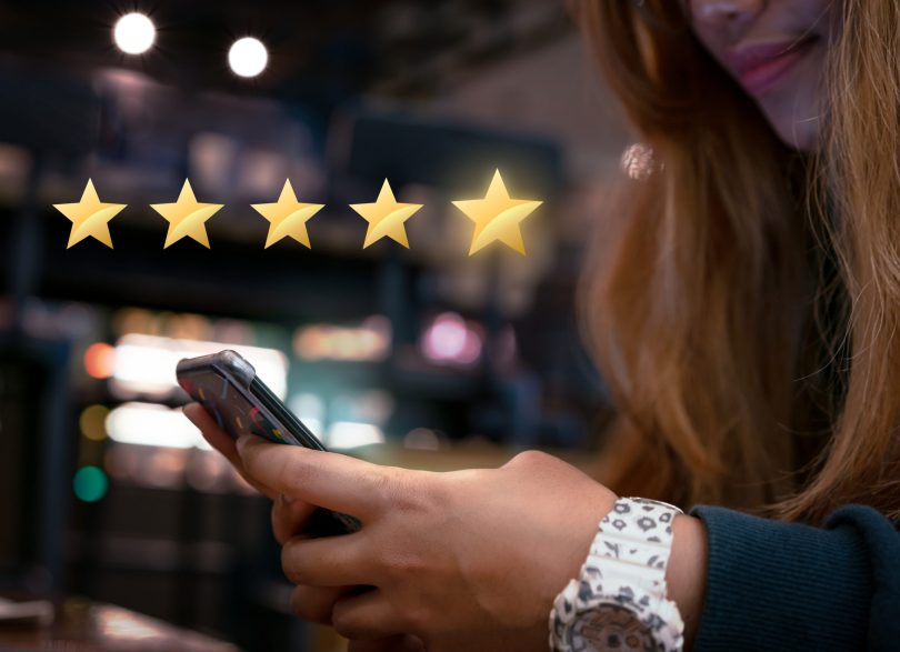 A happy customer giving a 5-star review for the salon services on discovery platforms using her mobile