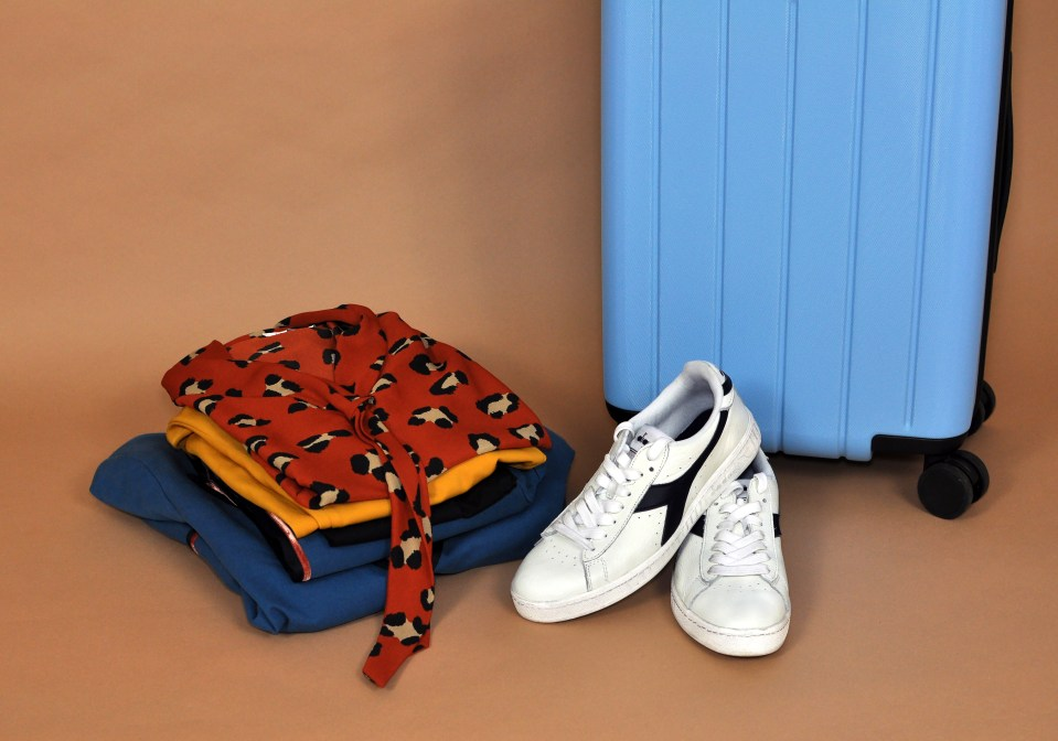 Suitcase with stack of bright women's clothes and sneakers