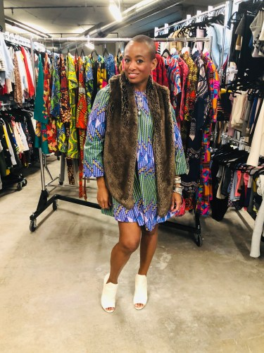 Erika Massaquoi, CEO and Designer at The OULA Company, styles The Pomp Wax Printed Dress - Geometric in purple with a faux fur vest, for a perfect fall look.