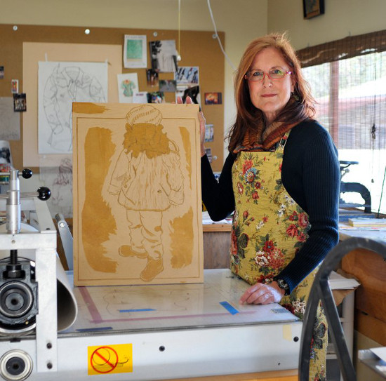 Artist Ouida Touchon stands at a printing press with an in-progress wood block.