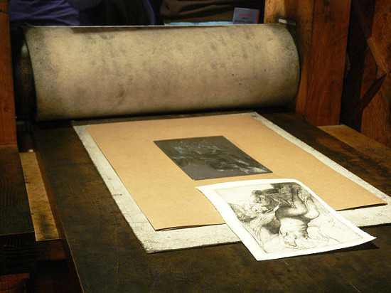 An intaglio plate and resulting print on a press. Photo by Remi Mathis (via Wikimedia Commons).